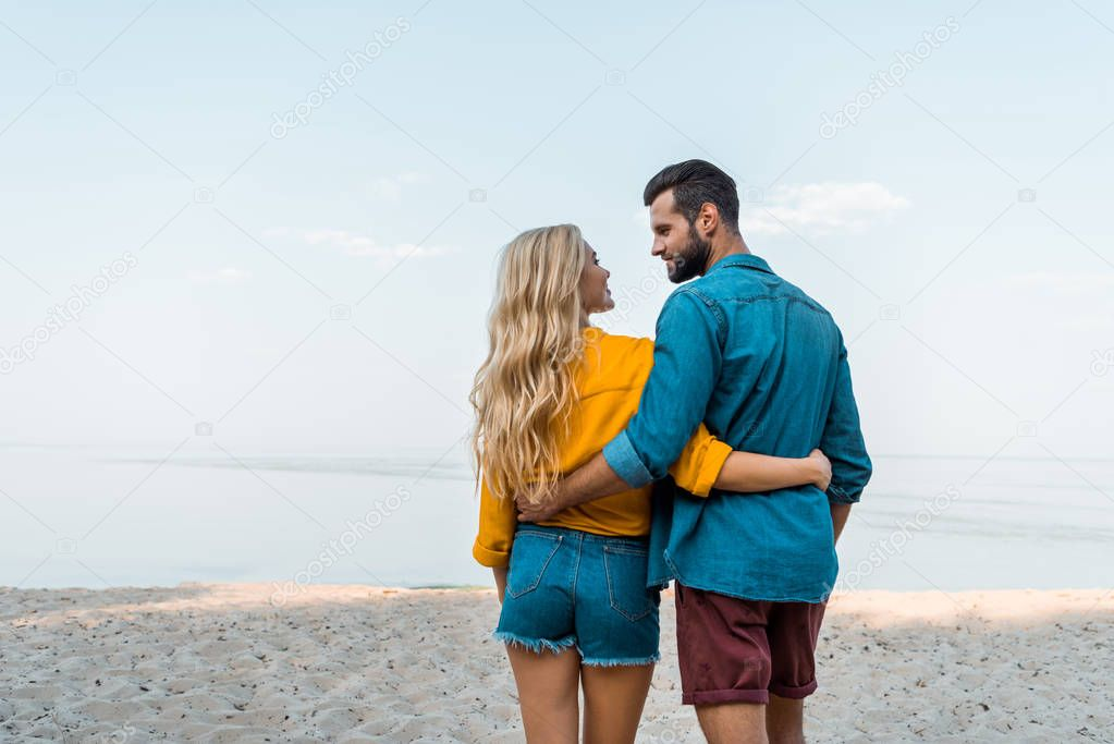 back view of couple hugging, walking and looking at each other on beach