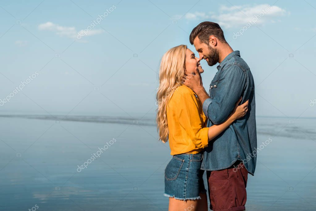 side view of smiling girlfriend and boyfriend touching with noses on beach