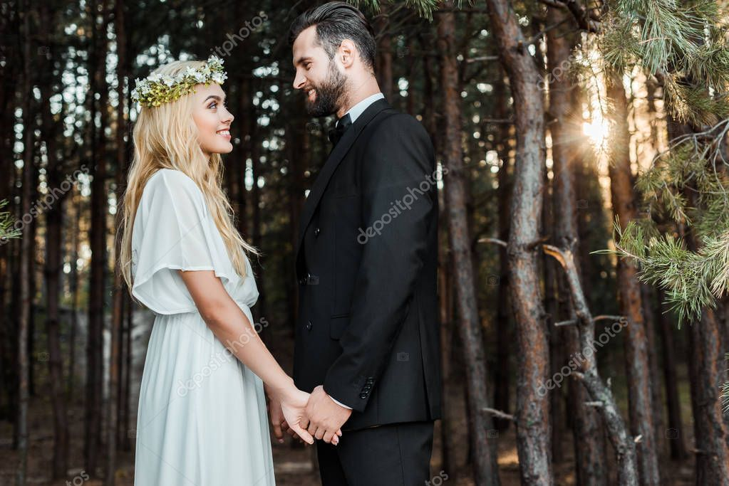 Side view of happy wedding couple holding hands and looking at each other during sunset in forest stock vector