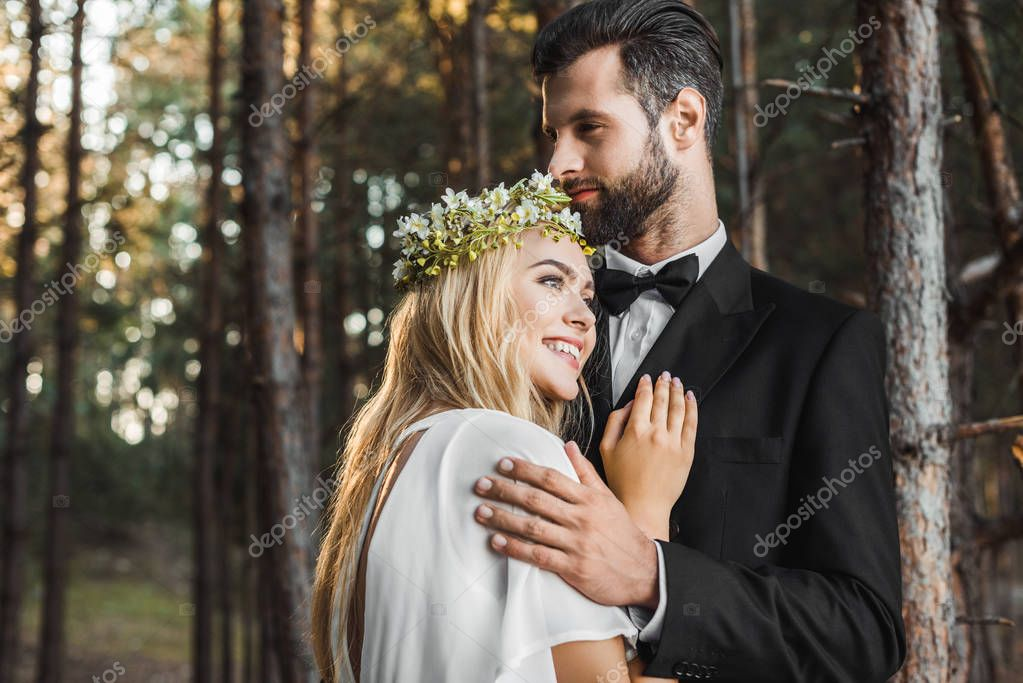 Beautiful smiling bride in white dress and handsome groom in suit hugging in forest stock vector