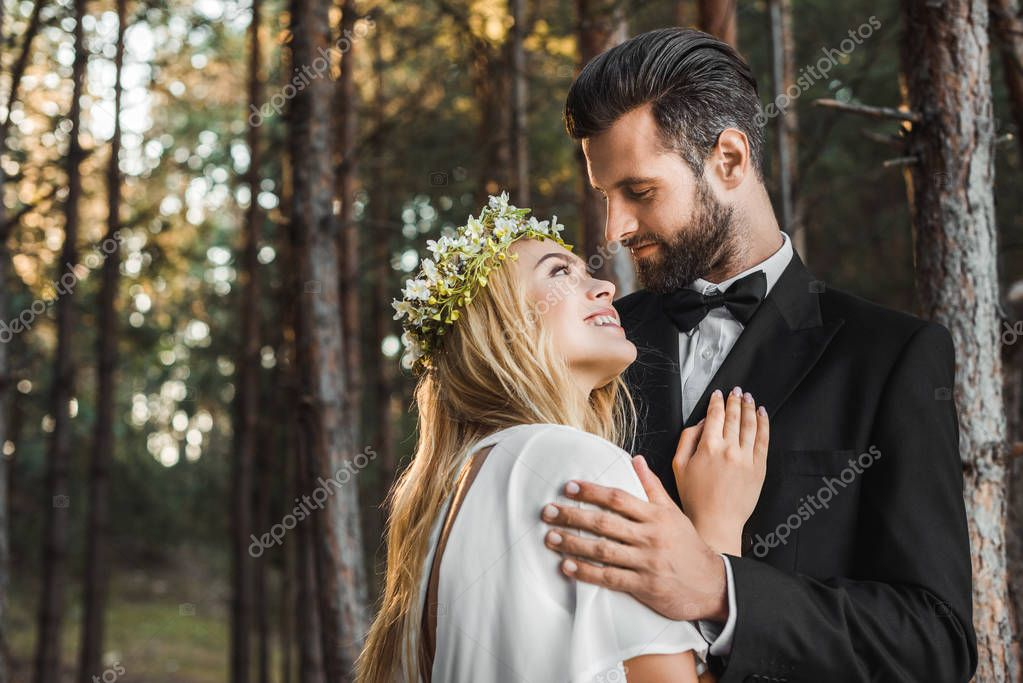 Beautiful bride in white dress and handsome groom in suit hugging in forest and looking at each other stock vector