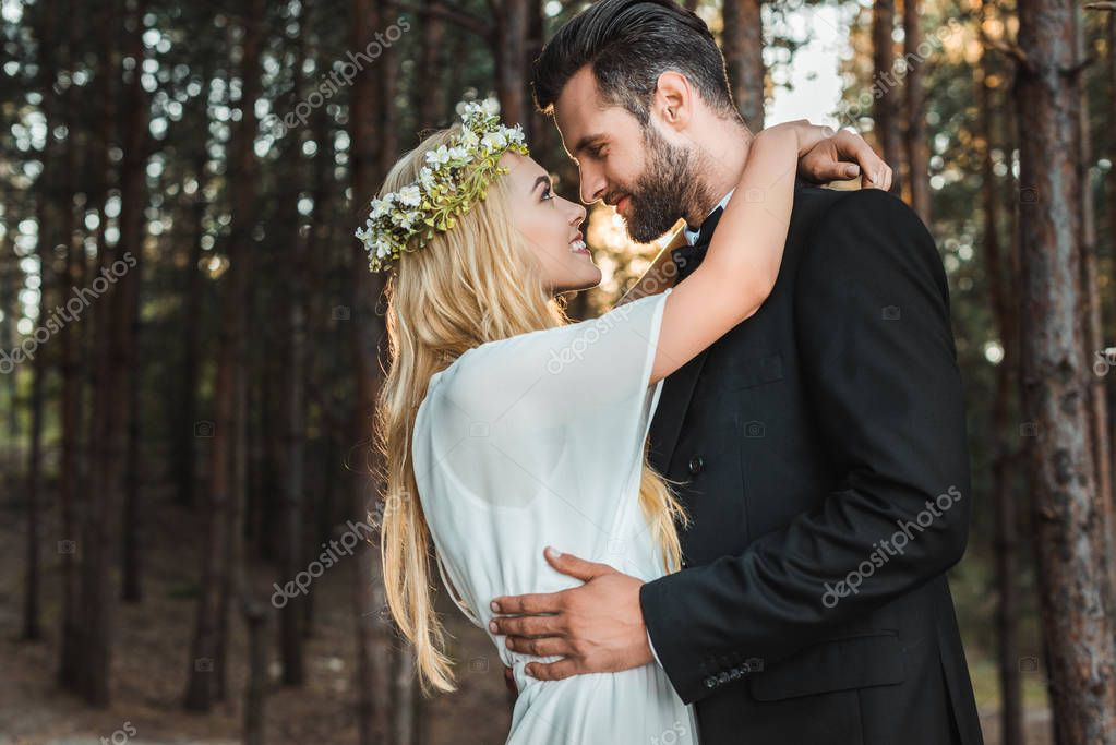 Beautiful happy bride in white dress and handsome groom in suit hugging and going to kiss in forest stock vector