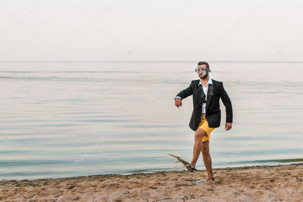 man in black jacket and shorts walking with swimming mask and flippers on sea shore