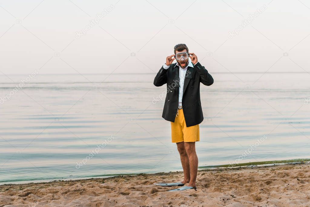 shocked man in black jacket, shorts and flippers wearing swimming mask on beach
