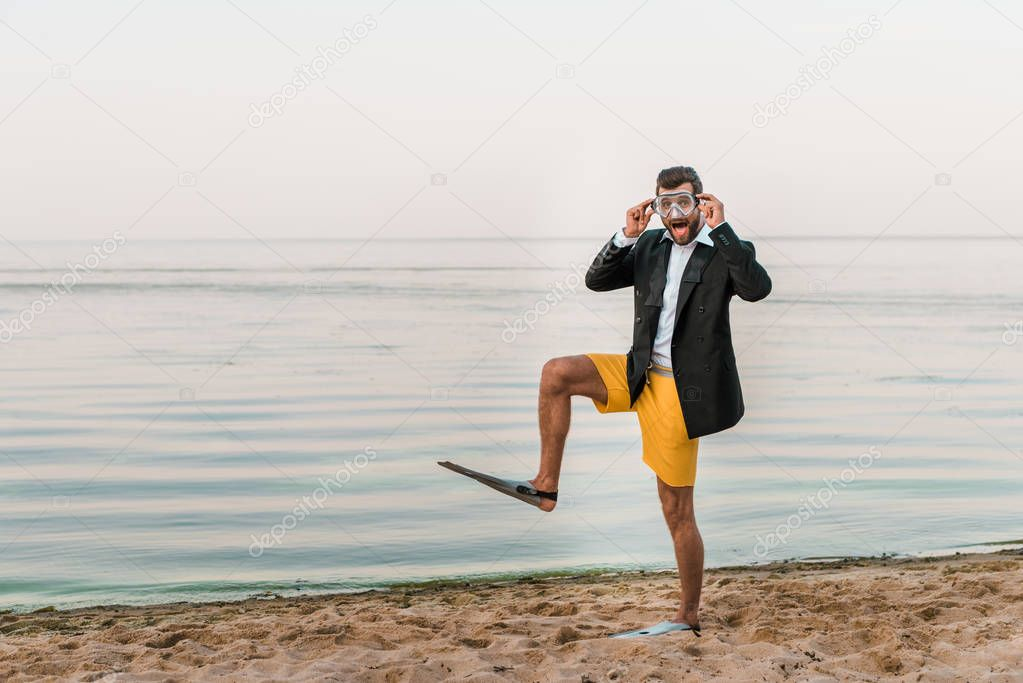 surprised man in black jacket, shorts and flippers touching swimming mask on beach near sea