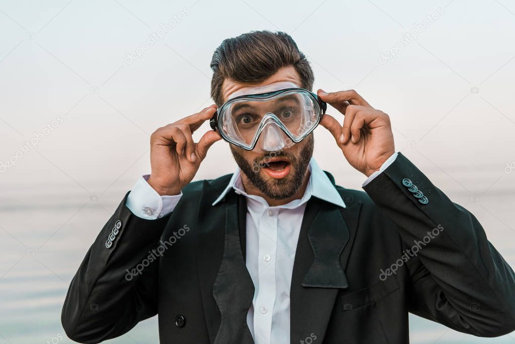 shocked man in black jacket and white shirt touching diving mask near sea