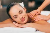 krásná mladá žena s květinou do vlasů s masáží v salonu spa