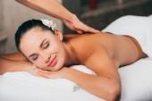 Fotografie mladá žena s květinou ve vlasech s masážní terapie ve spa salonu