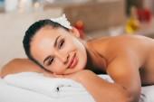 Fotografie glückliche Frau mit Blume im Haar, entspannen im Wellness-Salon und Blick in die Kamera