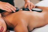 Fotografie oříznutý pohled mladé ženy s kamenné terapie v masážním salonu