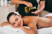 entspannende Frau bei Massage-Therapie mit Körperöl