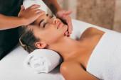 šťastná žena, odpočinek a mají masáž obličeje