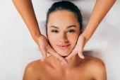 Fotografia donna attraente che si distende e avendo viso massaggio in centro massaggi