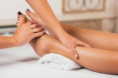 Photo cropped view of woman having feet massage therapy in spa salon