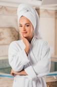 usmívající se žena v bílých froté župan s ručníkem na hlavě v lázeňském centru s bazénem