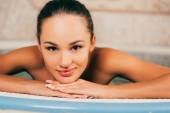 Fotografia donna attraente che riposa nella piscina nel salone della stazione termale e rivolto verso lobiettivo