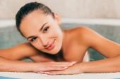Fotografia donna di rilassarsi in piscina, nel salone della stazione termale e rivolto verso lobiettivo