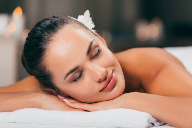 young woman with flower in hair sleeping at spa salon