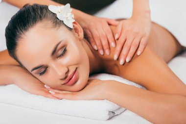 relaxing woman having massage therapy at spa salon