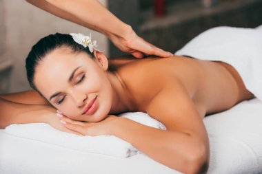 young woman with flower in hair having massage therapy at spa salon