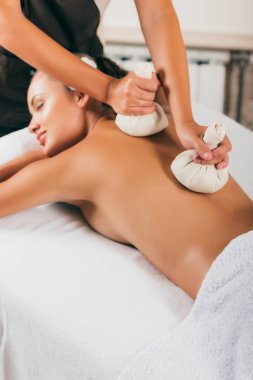 relaxing young woman receiving treatment at spa center