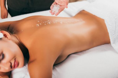 beautiful woman having salt therapy at spa salon