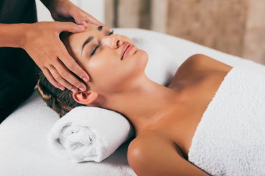 attractive woman relaxing and having face massage in spa center