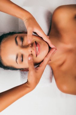 smiling woman relaxing and having face massage in massage salon