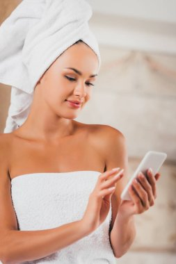 attractive woman using smartphone at spa salon