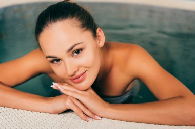 woman relaxing in swimming pool and looking at camera