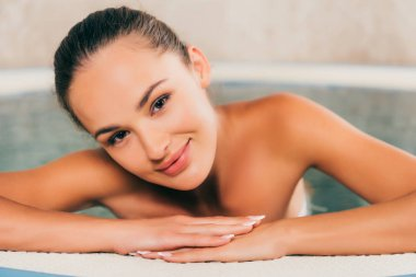 woman relaxing in swimming pool in spa salon and looking at camera