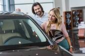 Fotografie young smiling couple choosing automobile at dealership salon