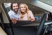 Fotografia Coppie sorridenti alla ricerca nella nuova vettura al salone di concessionaria