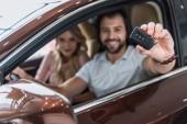 Selektivní fokus na usmívající se pár s auto klíčové sedí v novém autě v autorizovaném salonu