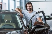 portrait of smiling man standing at new car in dealership salon