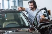 portrét usmívající se muž, který stojí na nové auto v autorizovaném salonu