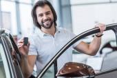 Fotografie Porträt von glücklicher Mann Auto Schlüssel liegt bei Neuwagen im Autohaus salon