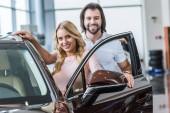 Porträt eines lächelnden Ehepaares, das vor einem Neuwagen im Autohaus steht