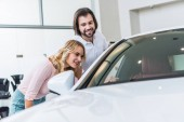 young couple checking new car at dealership salon