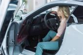 boční pohled na mladou ženu sedící v novém autě v autorizovaném salonu