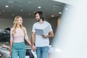 Fotografie junges Paar mit Katalog Auto im Autohaus Salon zu kaufen