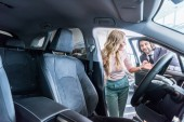 Fotografie seller in formal wear recommending automobile to woman at dealership salon