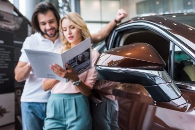 Selective focus of couple with catalog choosing car at dealership salon stock vector