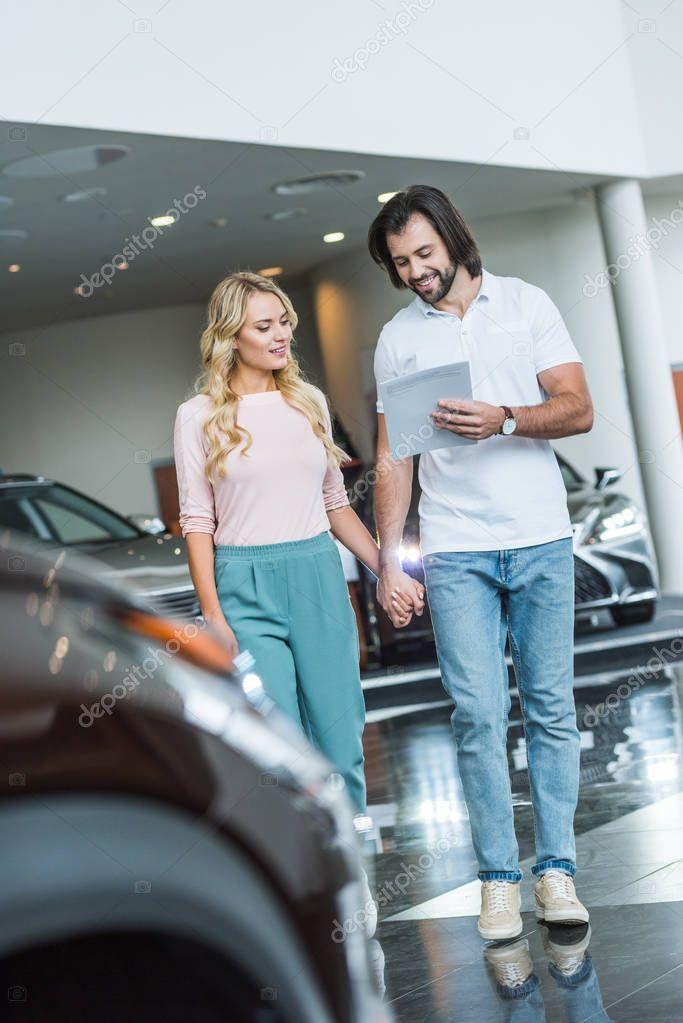 giovane coppia con catalogo acquisto auto presso concessionaria salone