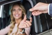 Teilansicht des Autohauses Salonverkäufer gibt Autoschlüssel an lächelnde Frau in Auto-Salon