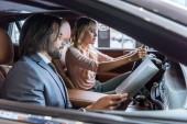 Fotografie Autohaus Salon Verkäufer und weibliche Kunden sitzen im Auto im Auto-salon