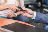 Fotografie cropped shot of dealership salon seller giving car key to woman in auto salon