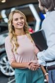 Fotografie částečný pohled na autorizovaném salonu prodavače a usmívající se zákaznici potřesení rukou v salonu auto