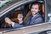 Fotografie happy businessman showing car key while sitting in new car in dealership salon