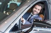 Fotografie portrét podnikatele v nové auto za zkušební jízdu v autorizovaném salonu